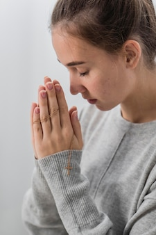 Vista laterale della giovane donna che prega a casa