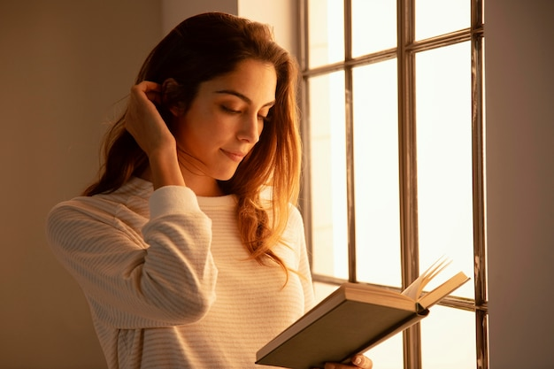 Side view of young woman reading a book at home