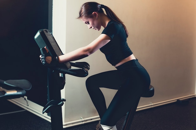 Side view of a young woman riding an exercise bike