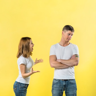 Side view of a young woman scolding to his boyfriend against yellow background