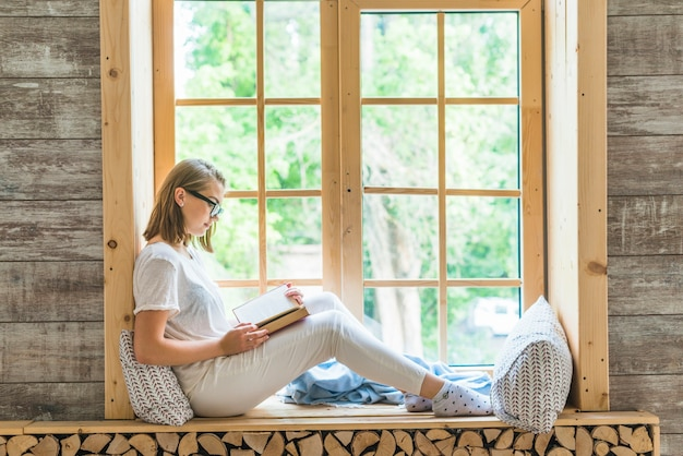 Side view of young woman sitting on window sill reading book