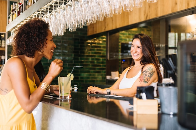 Side view of young woman smiling with female bartender at bar counter