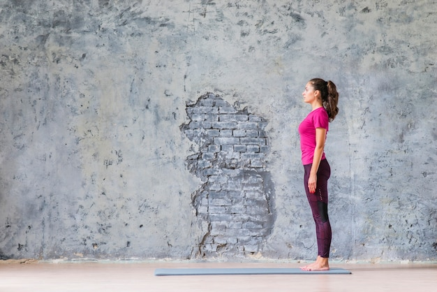 Side view of young woman standing on exercise mat against grey weathered wall