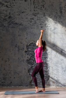 Side view of a young woman stretching on exercise mat against old gray wall