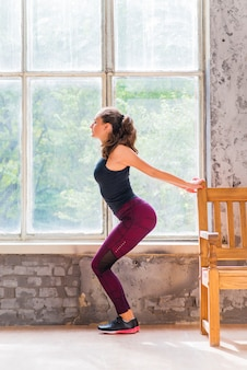 Side view of young woman stretching in front of window