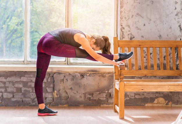 Side view of a young woman stretching her leg on bench near the window