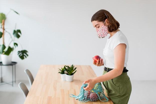 Вид сбоку молодая женщина, вынимающая продукты из сумки