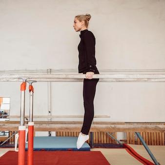 Вид сбоку тренировки молодой женщины для чемпионата по гимнастике