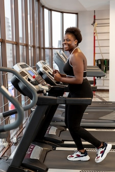 Side view young woman on treadmill