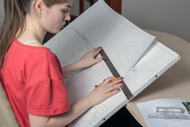 Side view of a young woman with a graphics tablet draws a sketch with a ruler and a pencil