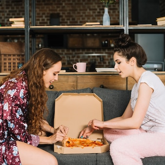 Side view of young women taking pizza slices from box