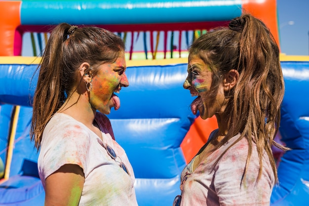 Side view of young women with holi color on their face sticking out tongue