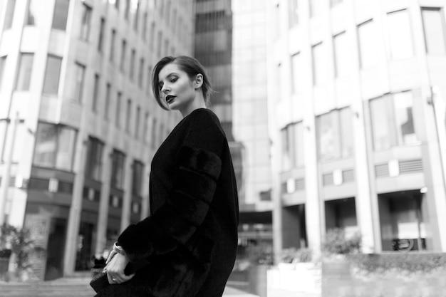 外でポーズをとる美しいスタイリッシュな女性のサイドバイリュー。毛皮のコートとクラッチを身に着けているファッショナブルな女の子。