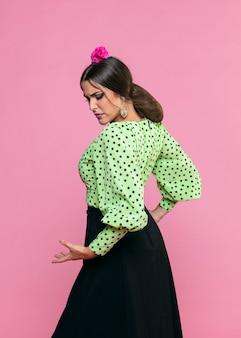 Side ways flamenca dancer on pink background