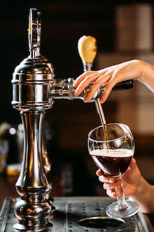 バーでグラスにドラフトビールを注ぐバーテンダーのside4ビュー