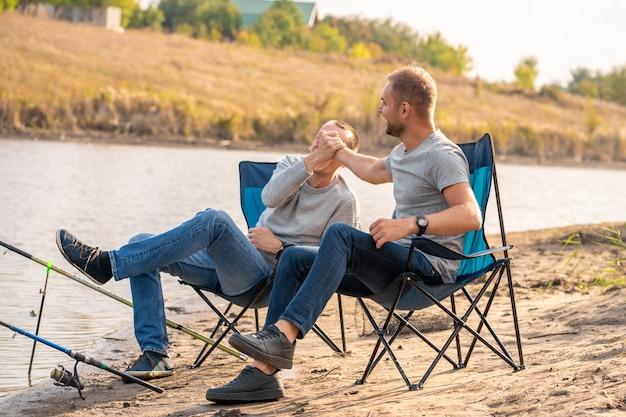 レジャーと人々。湖sideの桟橋で釣り竿と幸せな友達。