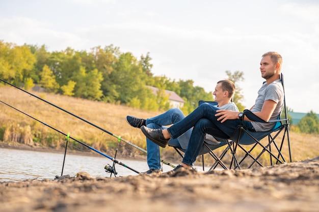 レジャーと人々の概念。湖sideの桟橋で釣り竿と幸せな友達。