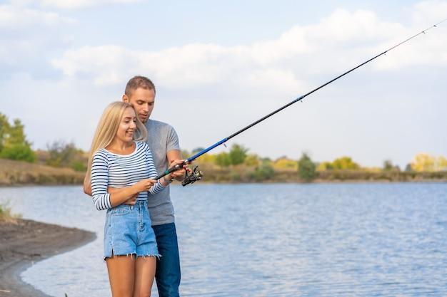 湖sideで幸せな若いカップル釣り