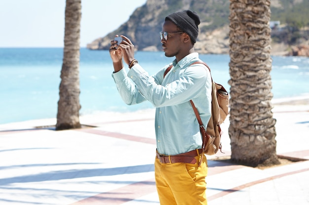 Sideview of fashionable young black traveler on vacations holding smartphone with both hands while taking pictures or recording video of beauty around him to post them on his social media accounts