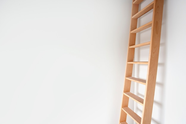 밝은 방에 있는 흰색 벽에 기대어 있는 나무 사다리의 현대적인 디자인의 세련된 계단