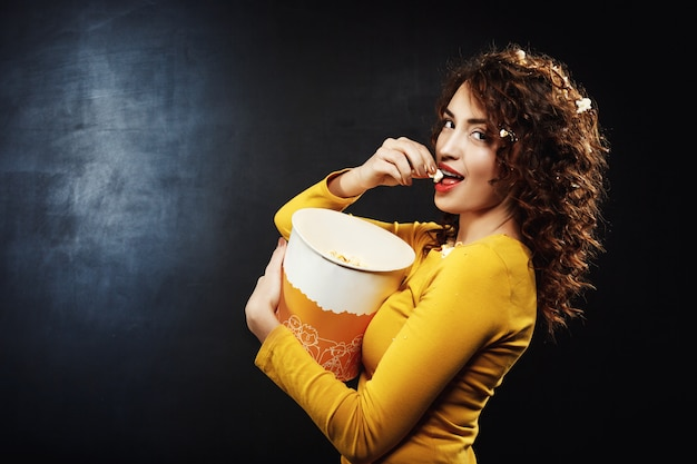 Вид сбоку удивительной молодой женщины едят попкорн в кинотеатре