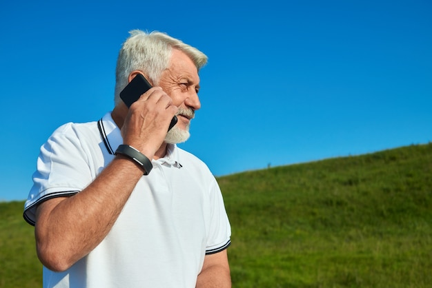 Sideview of sportsman talking on cellphone while sunny day.