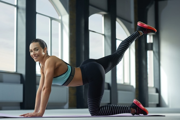 Sideview of sporty woman with strong body making exercises on gym floor.