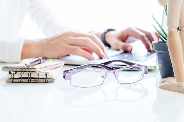 Sideview of white office desk with glasses and blur image man hand typing on laptop.