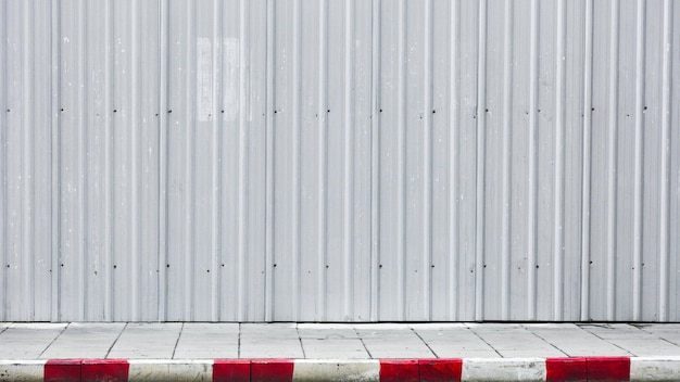 Sidewalk and curb red-white with metal corrugated wall
