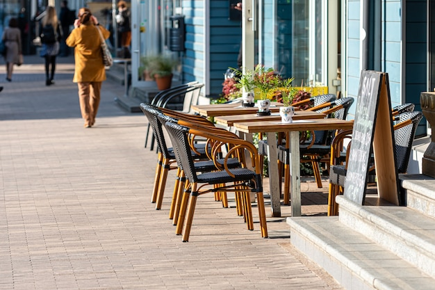 Sidewalk open air cafe with empty chairs and  tables