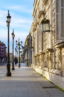 Sidewalk of the street of the royal palace of madrid with street lamps and old building in sunny day. spain.