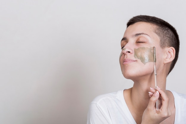 Sideway woman applying on cheek mud treatment