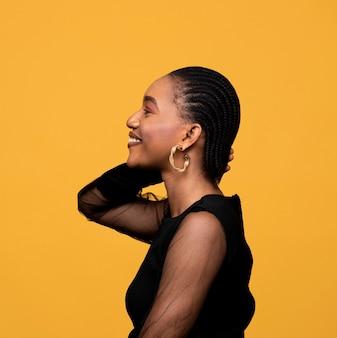 金色のイヤリングと横向きのアフリカの女性
