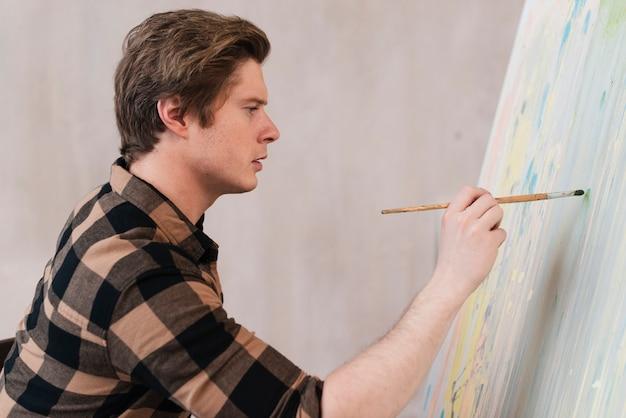 Sideways artist man painting on canvas