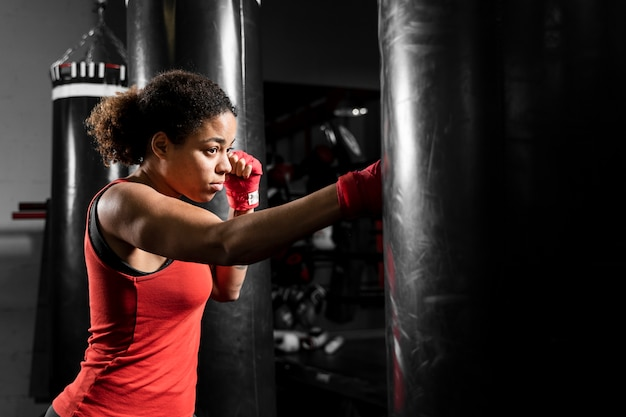 Sideways athletic woman training in boxing center