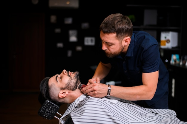 Sideways barber cutting client's beard