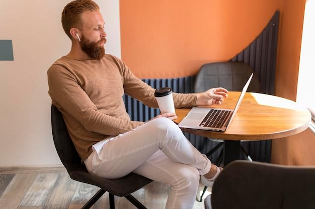 Боковой бородатый мужчина работает на ноутбуке