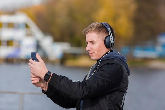 Sideways blonde man listening to music outdoors
