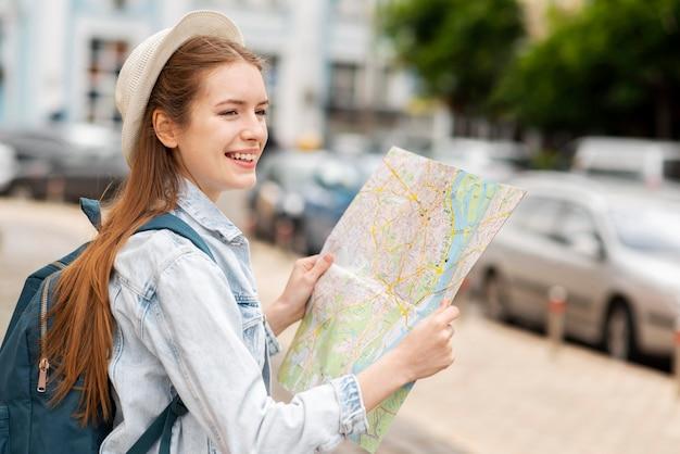 地図を持っている横向きの都市旅行者
