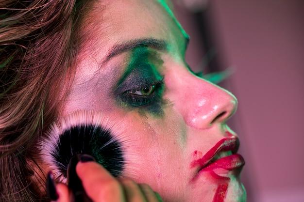 Sideways close-up portrait of a woman using a brush