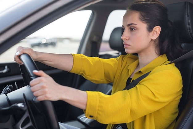 Боком уверенная женщина за рулем