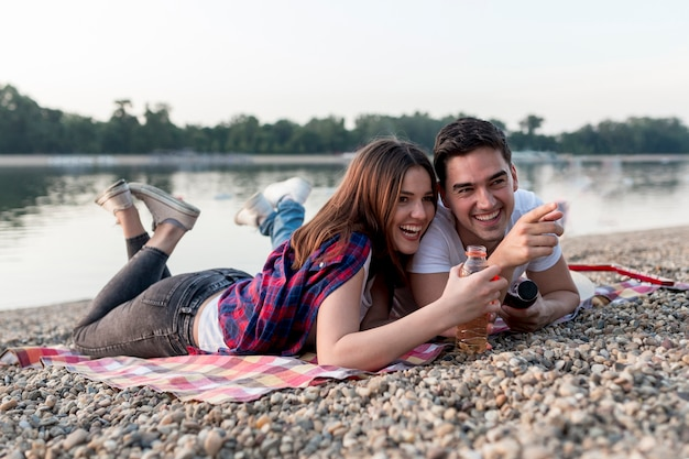 Sideways couple on a date lying on picnic blanket