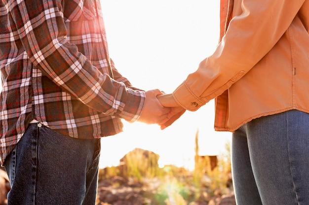 日没で手をつないで横向きのカップル