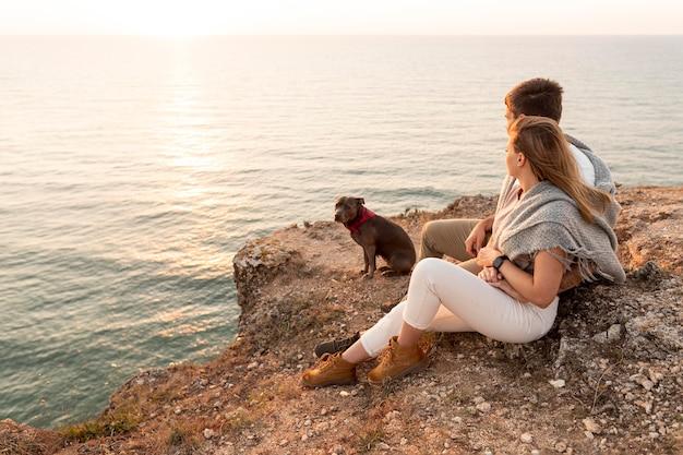 海岸で犬の隣に座っている横向きのカップル