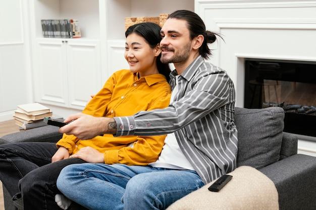 Пара боком сидит на диване и смотрит телевизор