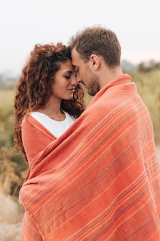 Sideways couple wrapped in blanket