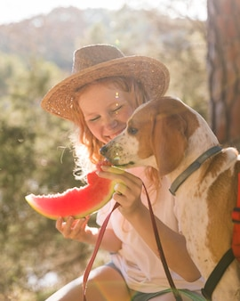 Sideways dog and woman eating a slice of watermelon