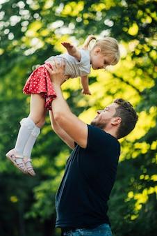 横になっている父と娘が公園で遊んで