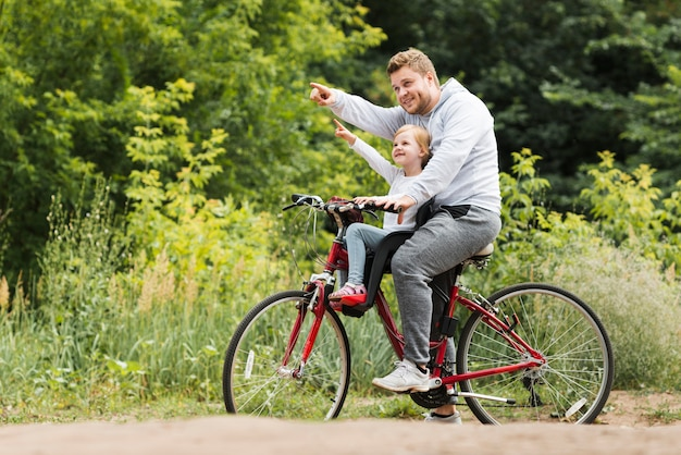 Sideways father and daughter on bicycle