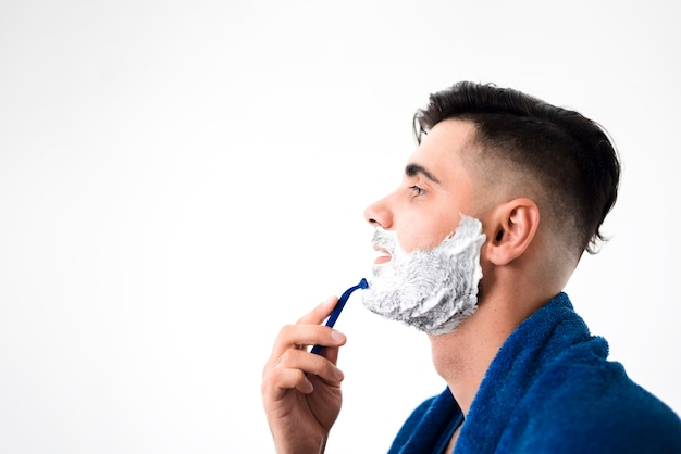 Sideways handsome man shaving his beard close-up
